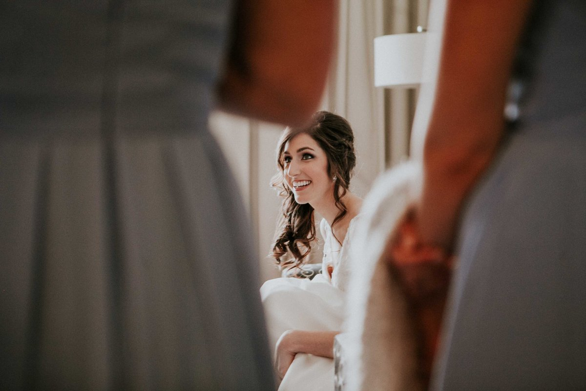 Bride smiles at bridesmaids as she puts on her shoes in hotel indigo in Columbus indiana