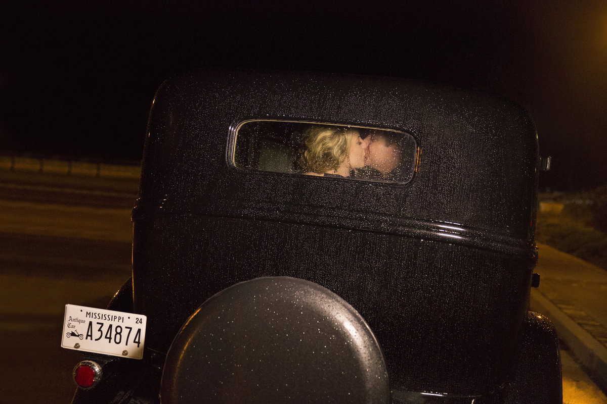 Bride and Groom share a kiss in back of classic car during reception exit at the biloxi visitors center