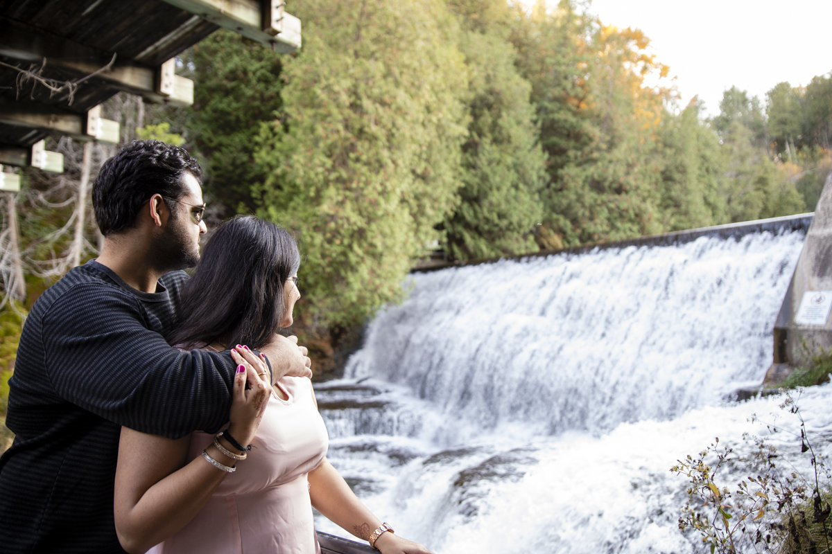 Engaged couple looking at the waterfalls at the Forks of the Credit River in Belfountain