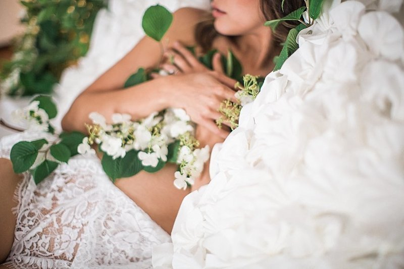 photo of woman on bed covered in a floral garland and white bridal romper from forever 21