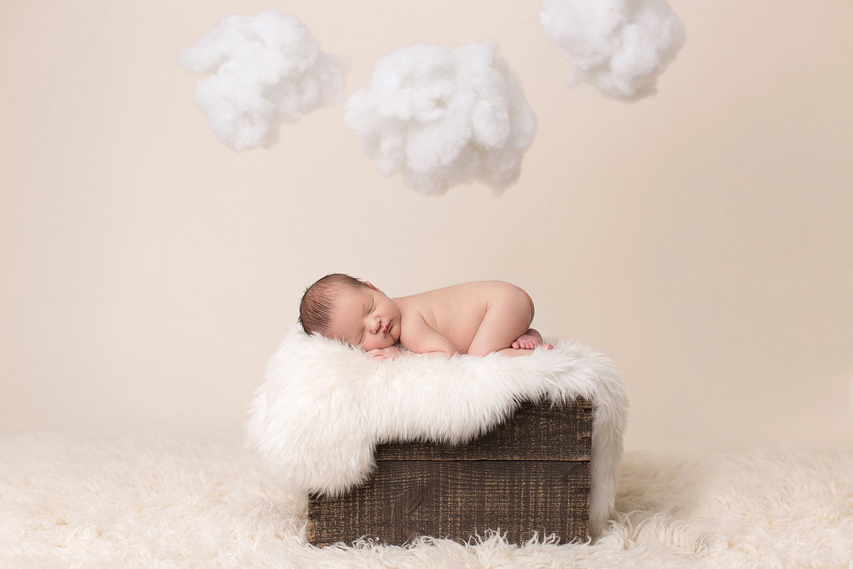 Newborn posed on wood  box with fluffy white handing clouds
