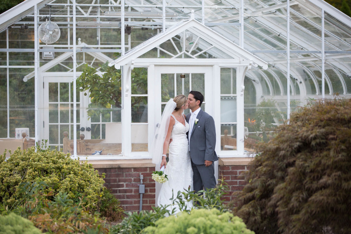 bride and groom in front of greenhouse at The pond House