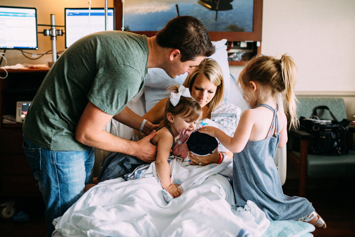 family cuddled together in delivery room