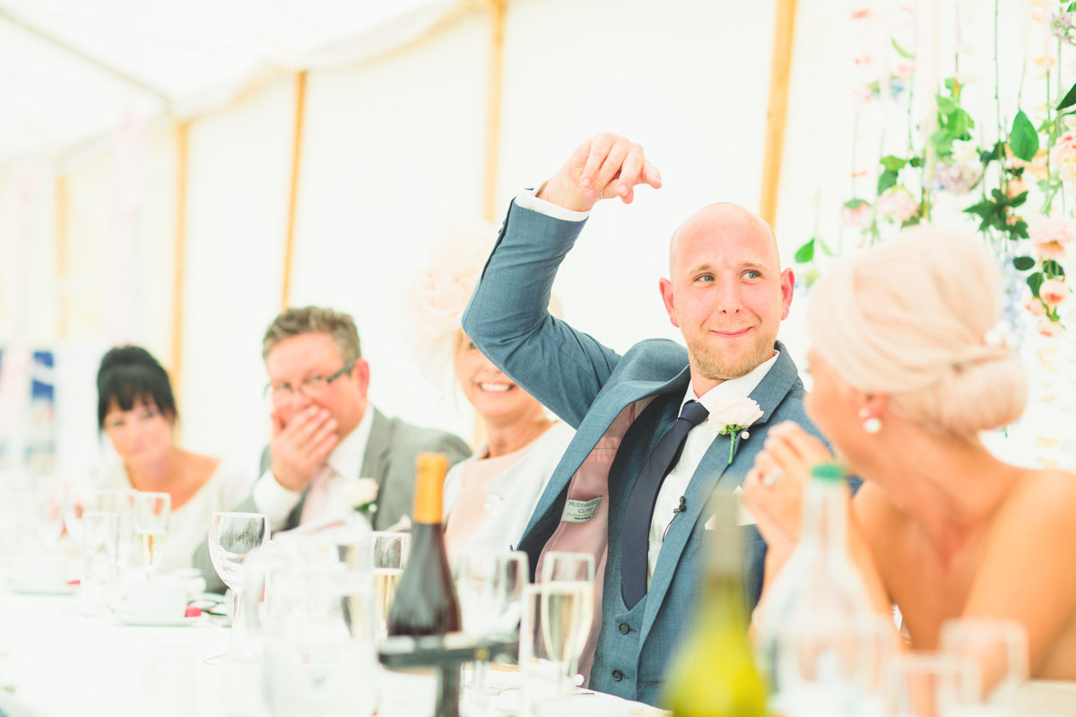 groom is laughing in a speech