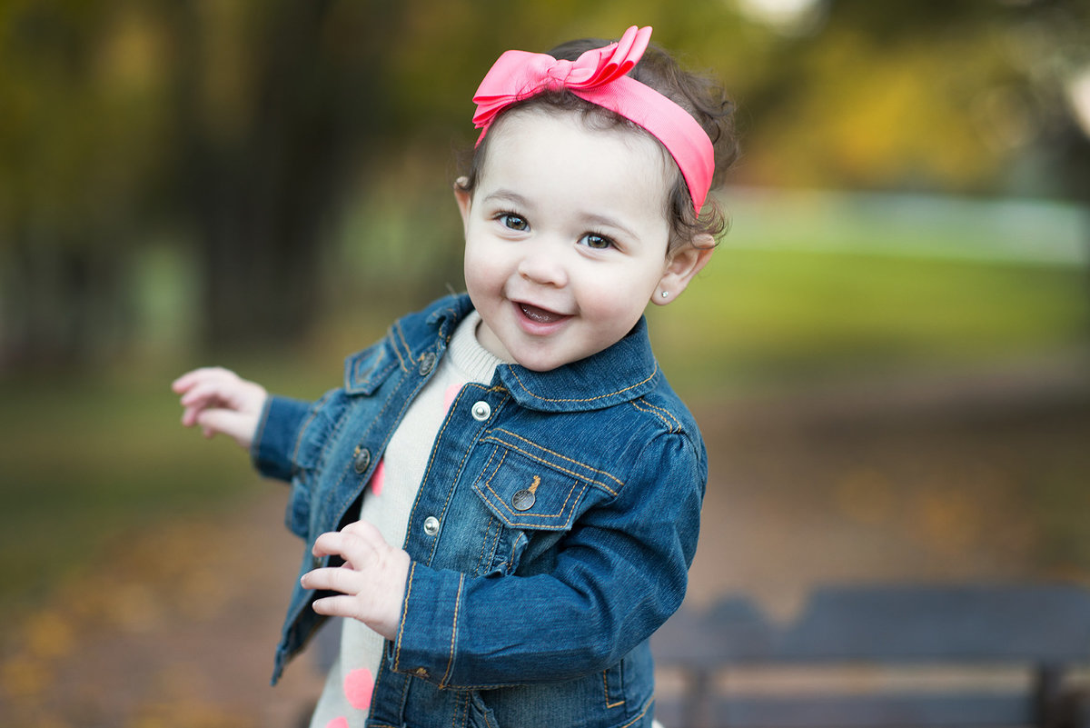 a toddler girl smiling at the camera during fall