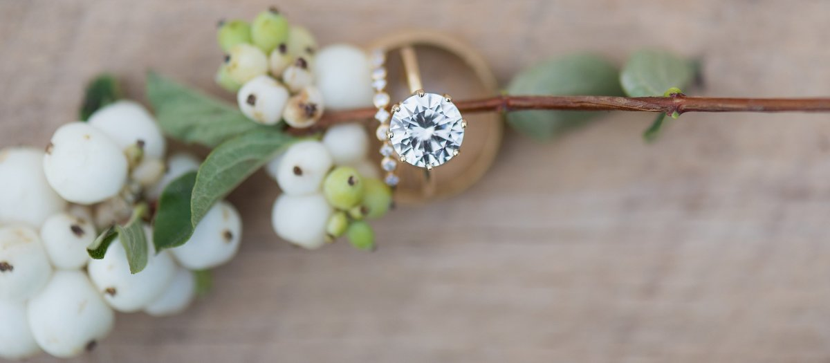 Gold Wedding Rings with white berries on wood farm table photo