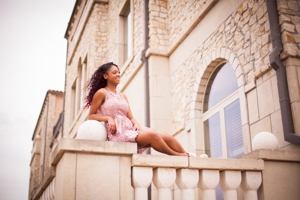 High school senior portrait of girl on ledge at castle building at Adriatica Village in McKinney Tx
