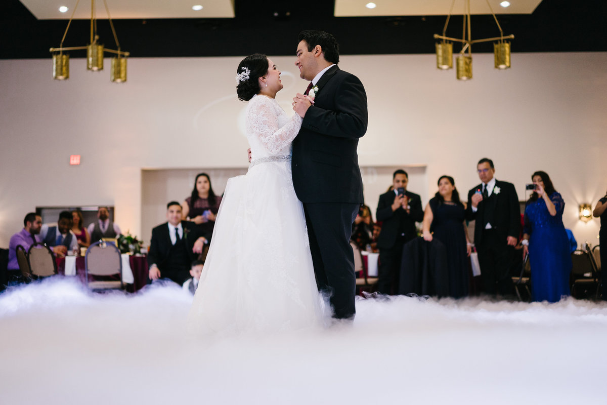 Bride and Groom have first dance in smoke fog at wedding reception at San Fernando Hall in down town San Antonio