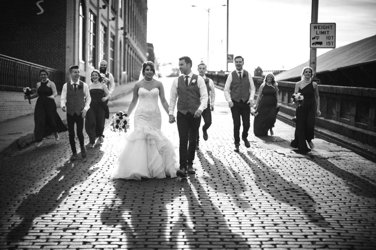 Bride and groom with their bridal party walking down cobble stone road at Jackson Terminal Wedding Venue by Knoxville Wedding Photographer, Amanda May Photos.