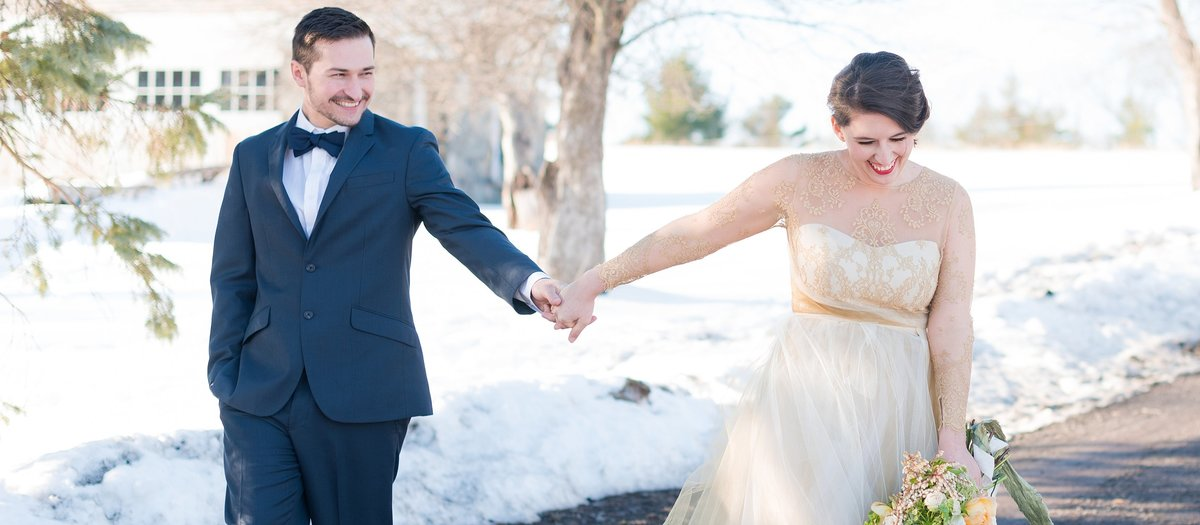 Bride and groom laughing and walking in the snow photo