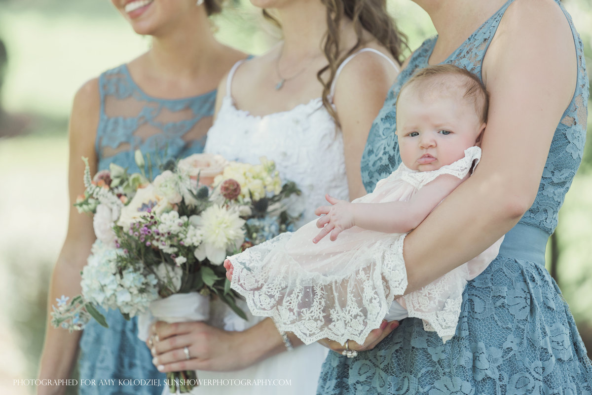 charlotte wedding photographer jamie lucido captures a side detail of a bridesmaid holding a baby and the bride holding her bouquet