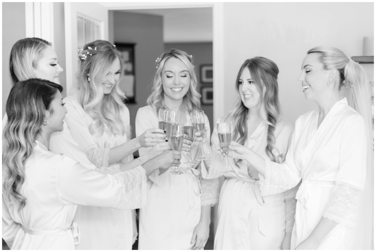 Light-and-Airy-Ottawa-Wedding-Photographer-bride-and-bridesmaids-drinking-champagne