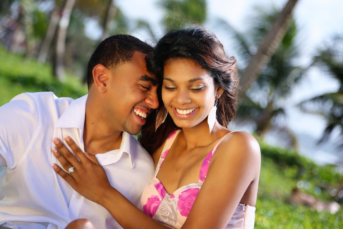Couple laughing together with woman's hand on man's chest displaying her engagement ring. Photo by Ross Photography, Trinidad, W.I..