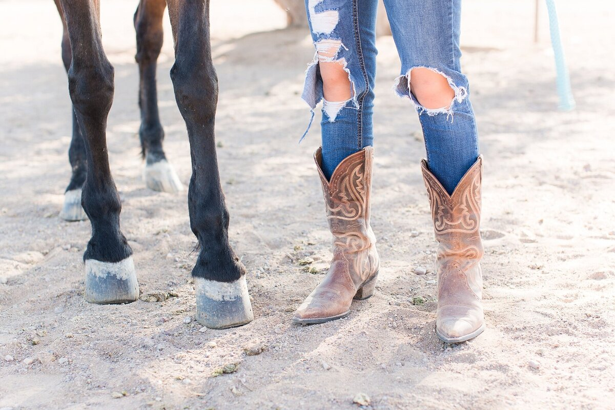 close up of a girl in cowboy boots next to her horse's legs
