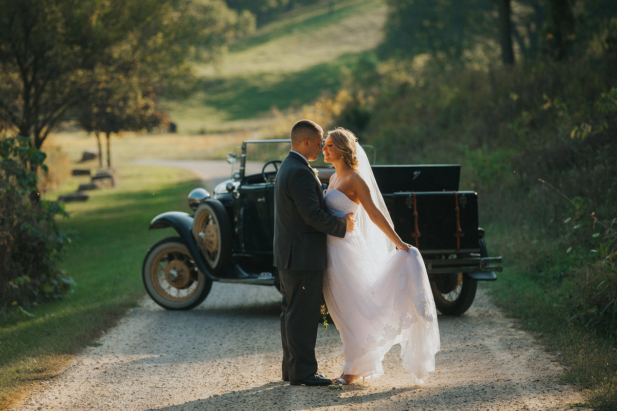 bride and groom kissing with classic car at oak hill
