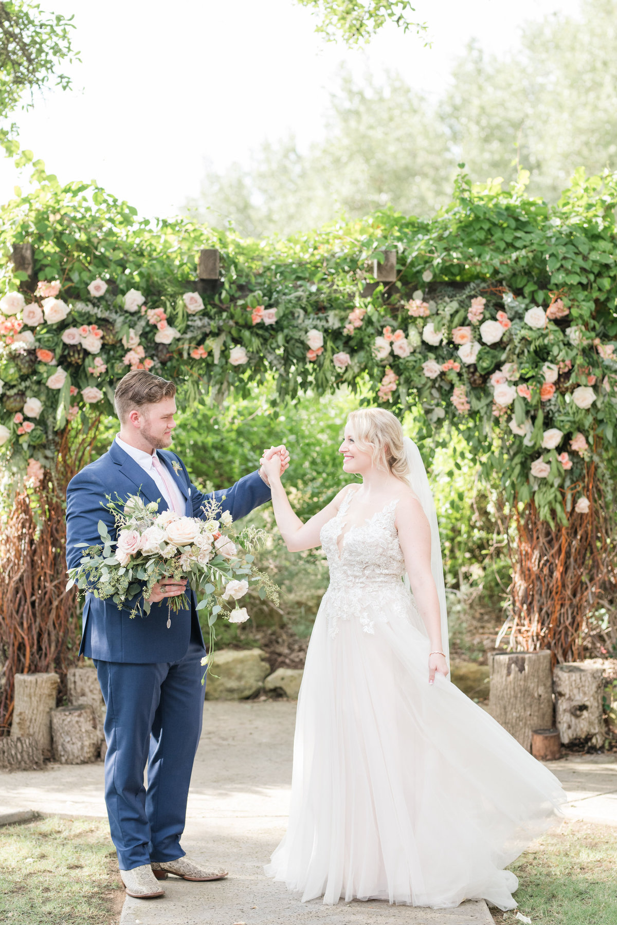 Bride spins by Petal Pushers wedding floral arbor at Vista West Ranch