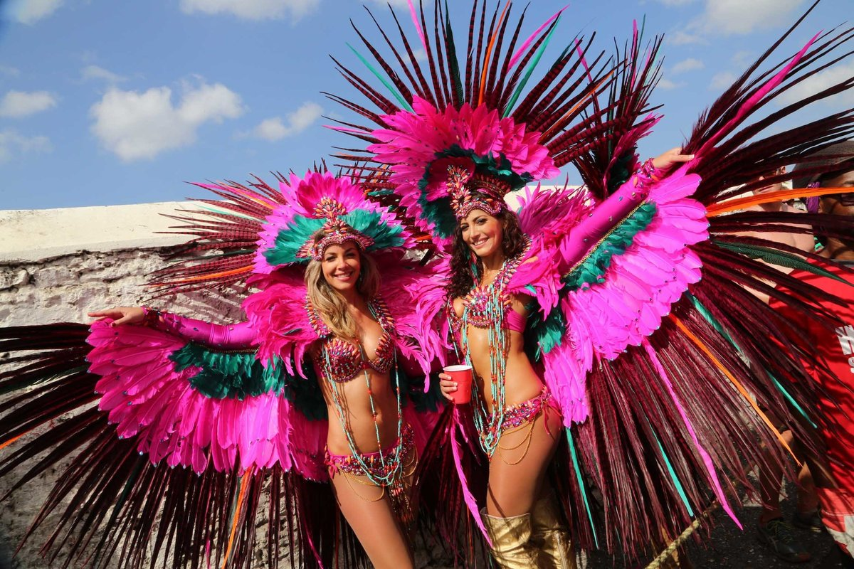Two ladies playing mas strike a pose in striking pink and feathered costumes. Photo by Ross Photography, Trinidad, W.I..