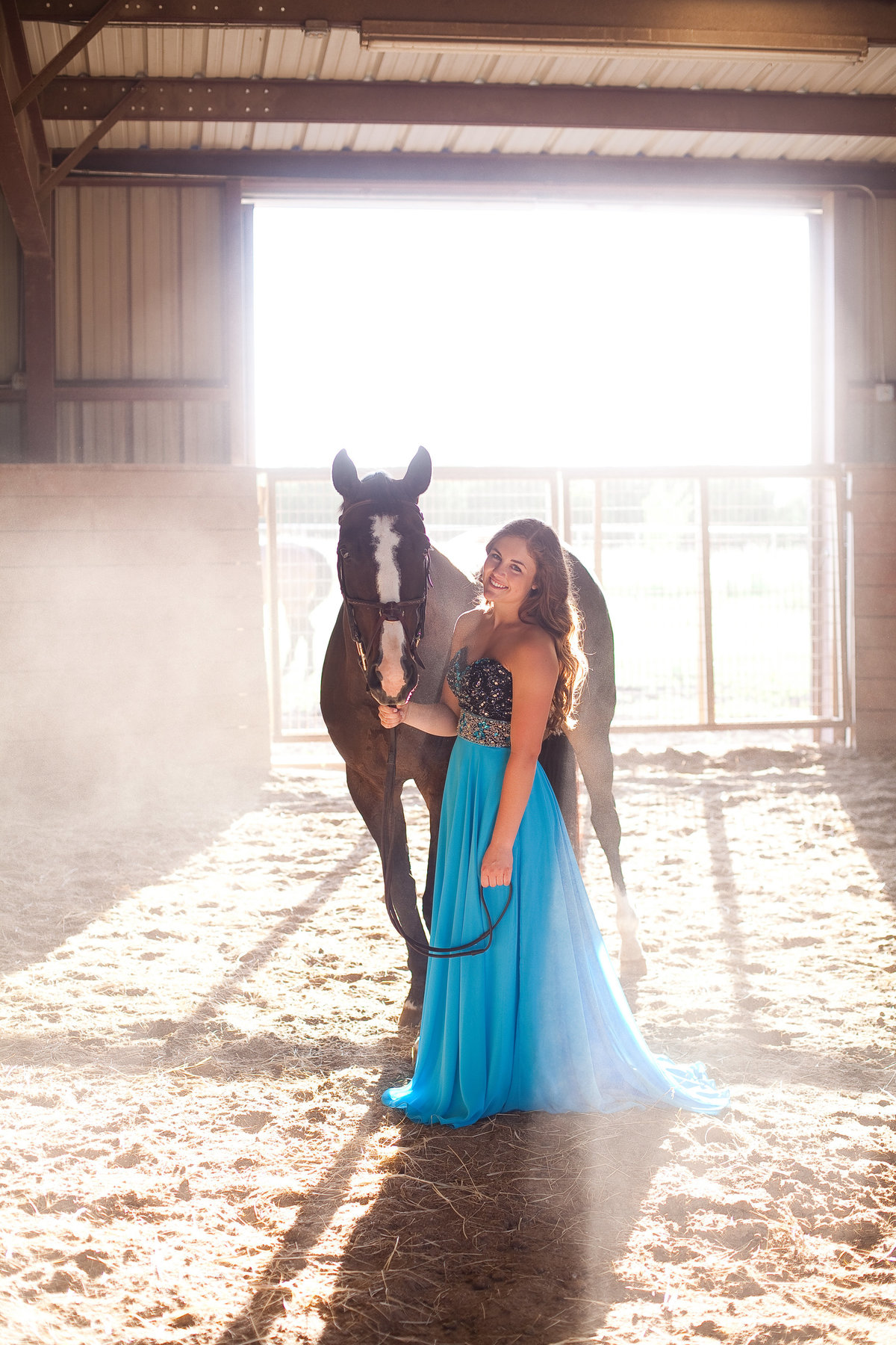 Senior Picture of girl in blur formal dress with horse in barn at sunset