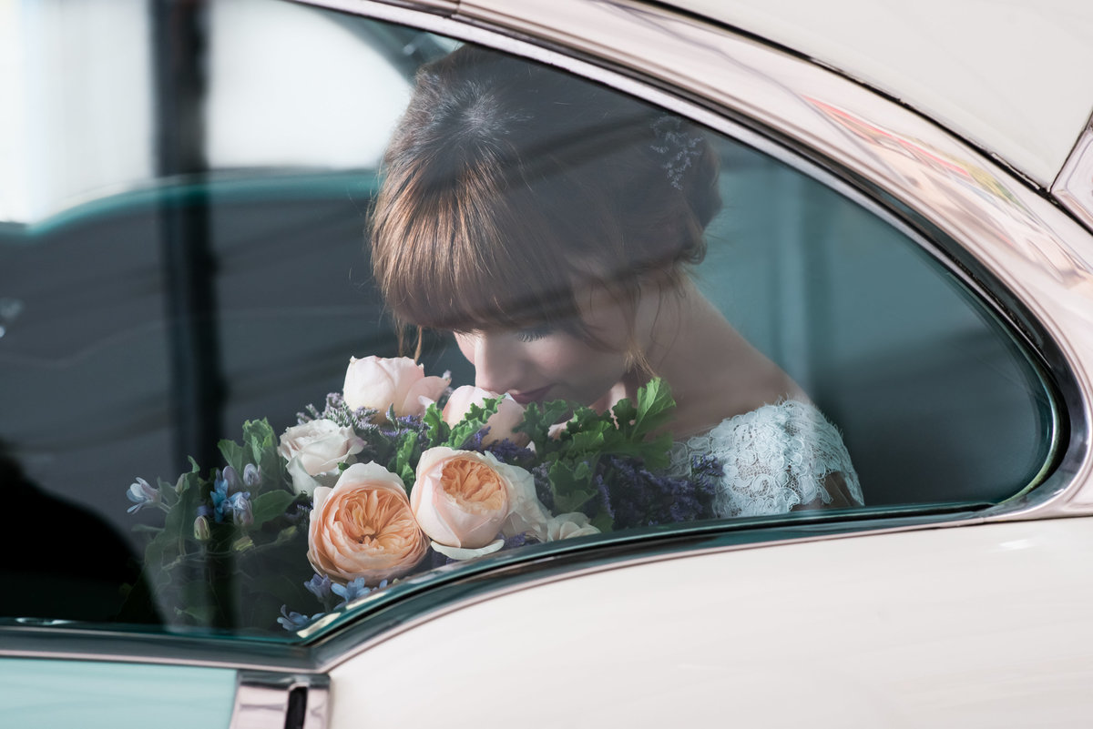 Bride smelling bouquet as she waits to exit car prior to wedding