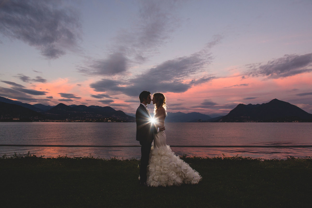bride in groom in front of lake como as the sunset goes down