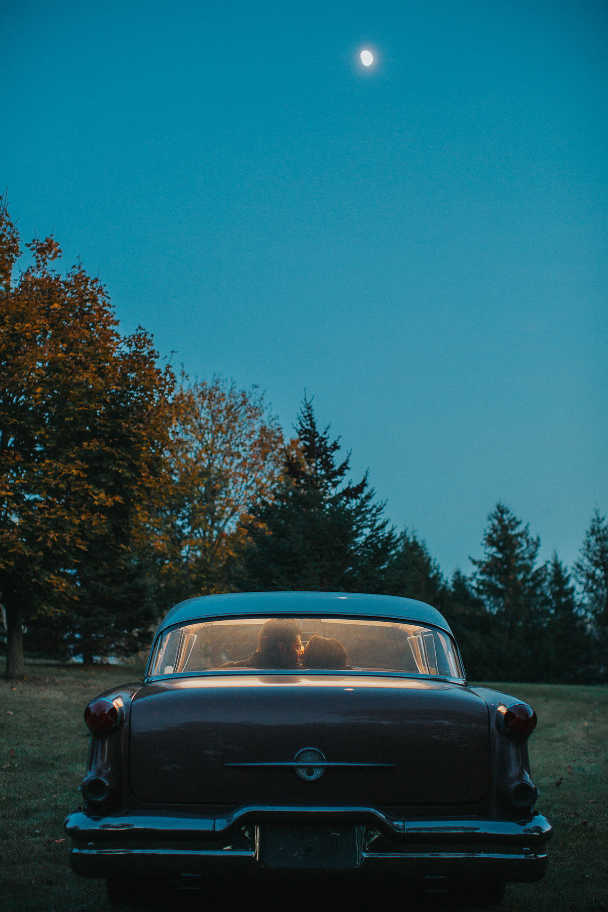 couple kissing in the back of a classic car at night during their engagement photographs