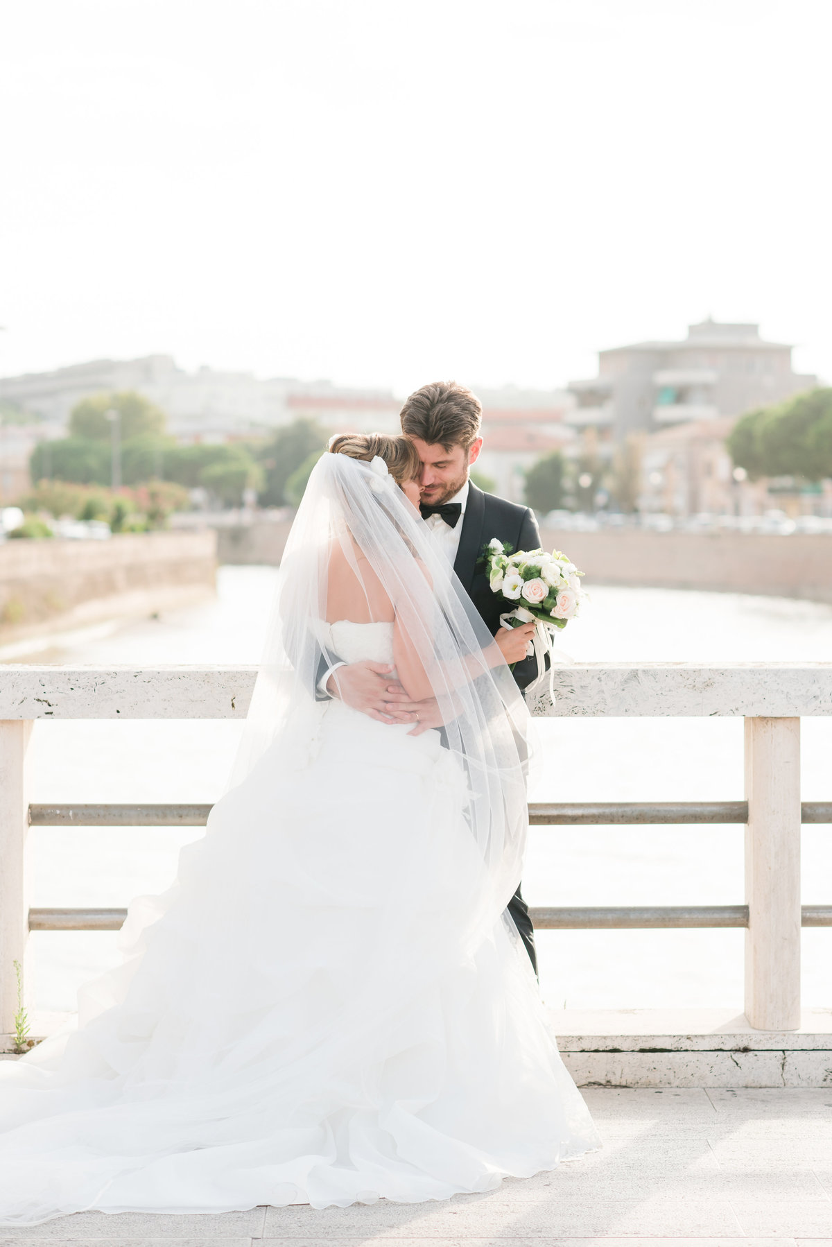 a bride wearing a strapless dress with cathedral length veil being held by her husband wearing black tie suit with bowtie on a bridge in downtown Sengillia Italy
