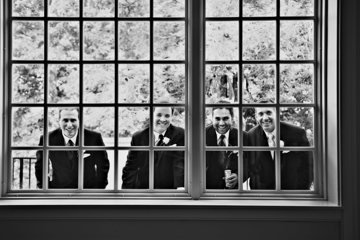 Groomsmen look through the window at wedding guests before the ceremony at Radnor Valley Country Club