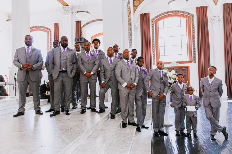 Groomsmen in gray suits lined up in  inside church