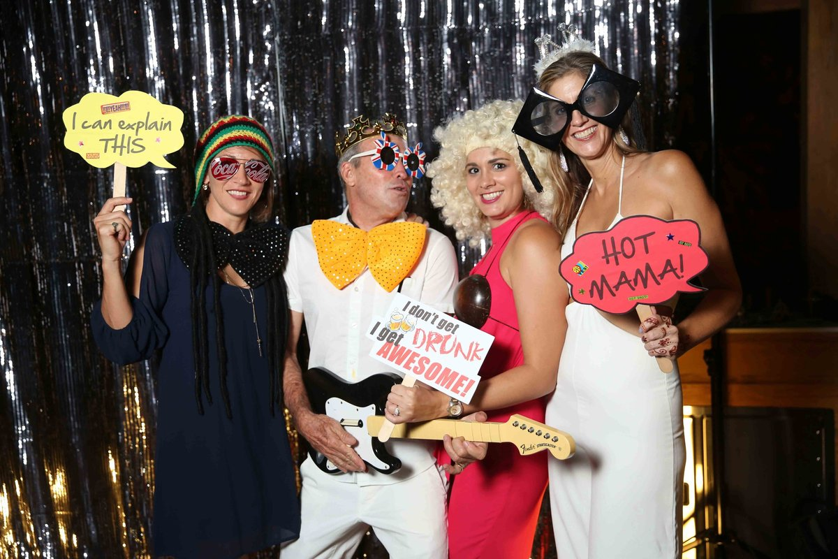 A foursome enjoy amusing signs in front of silver photobooth backrop. Photobooth by Ross Photography, Trinidad, W.I..