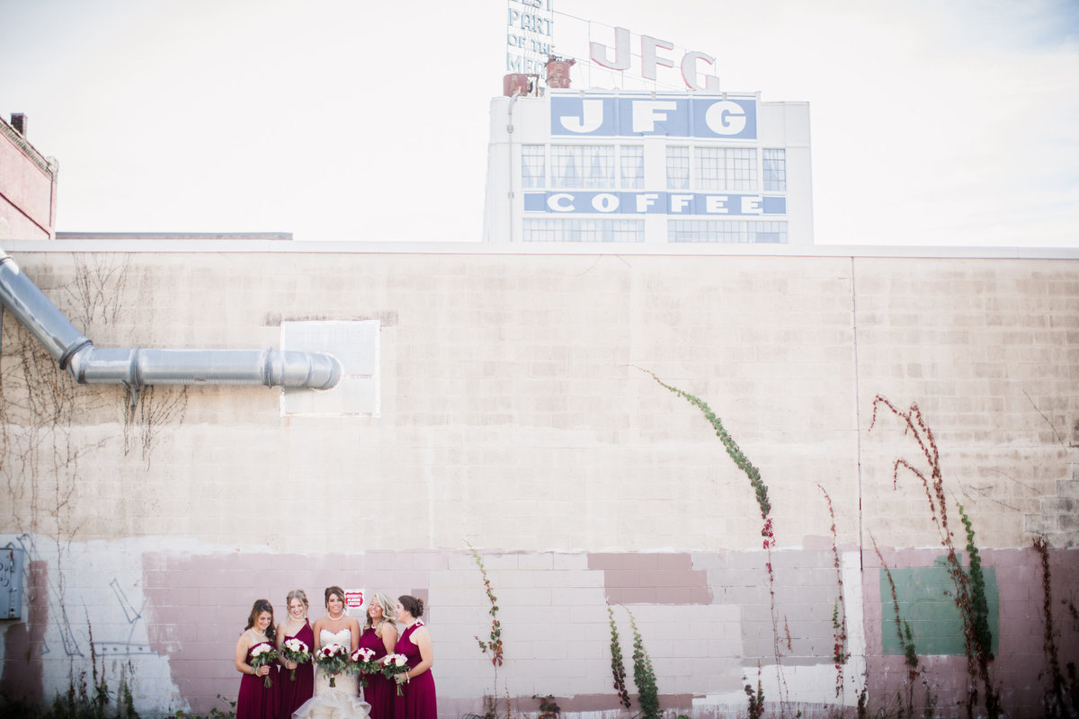 Bride and bridesmaids standing in front of JFG sign at Jackson Terminal Wedding Venue by Knoxville Wedding Photographer, Amanda May Photos.