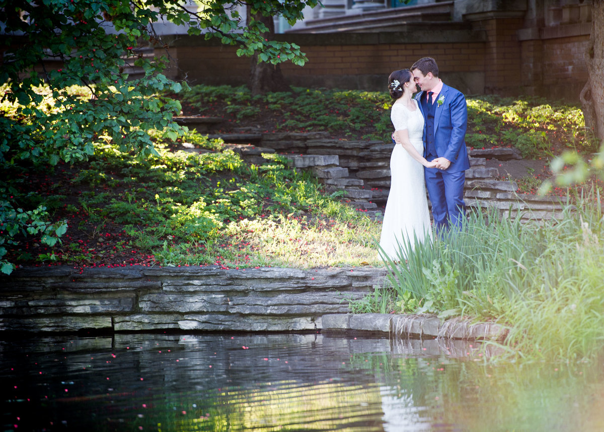 Bride and groom kiss by water, Columbus Park Refectory, Chicago.