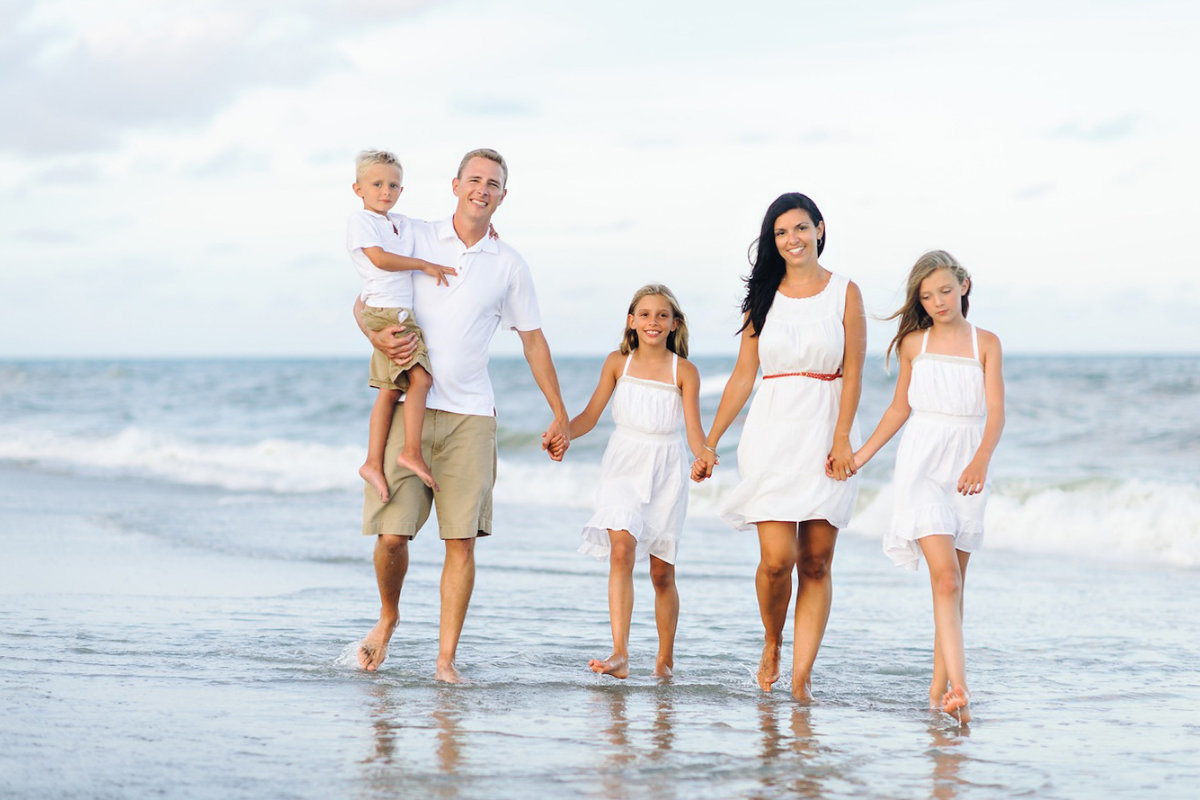 All white outfits – Mrytle Beach Family Pictures. Family walking on the beach during their family session by Pasha Belman