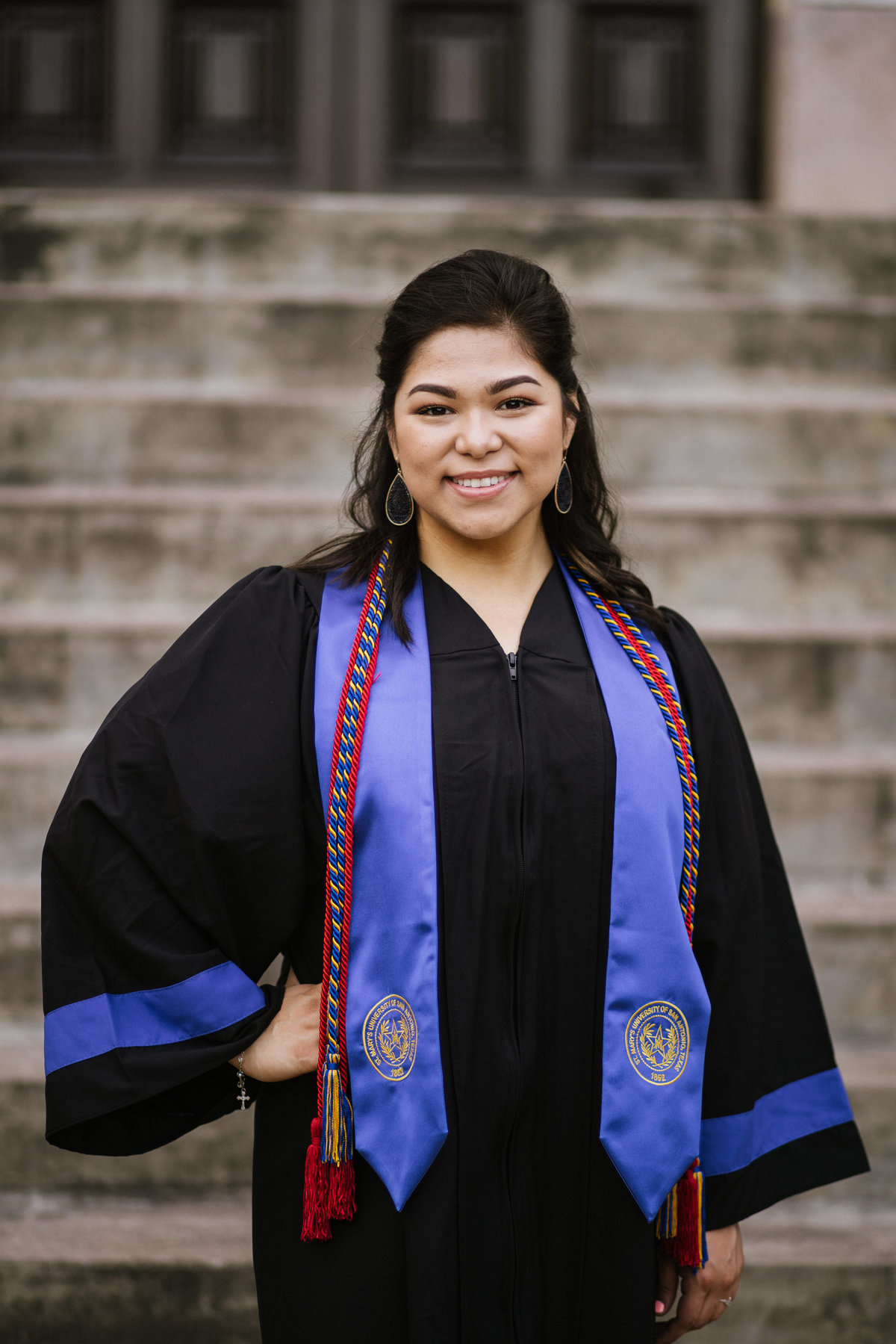 college senior posing with her cords and cap and gown by San Antonio senior photographer