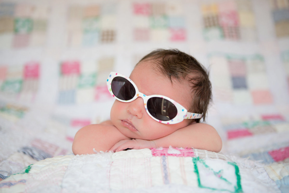 Newborn girl wearing sunglasses sitting on a quilt for her newborn pictures by Knoxville Wedding Photographer, Amanda May Photos.