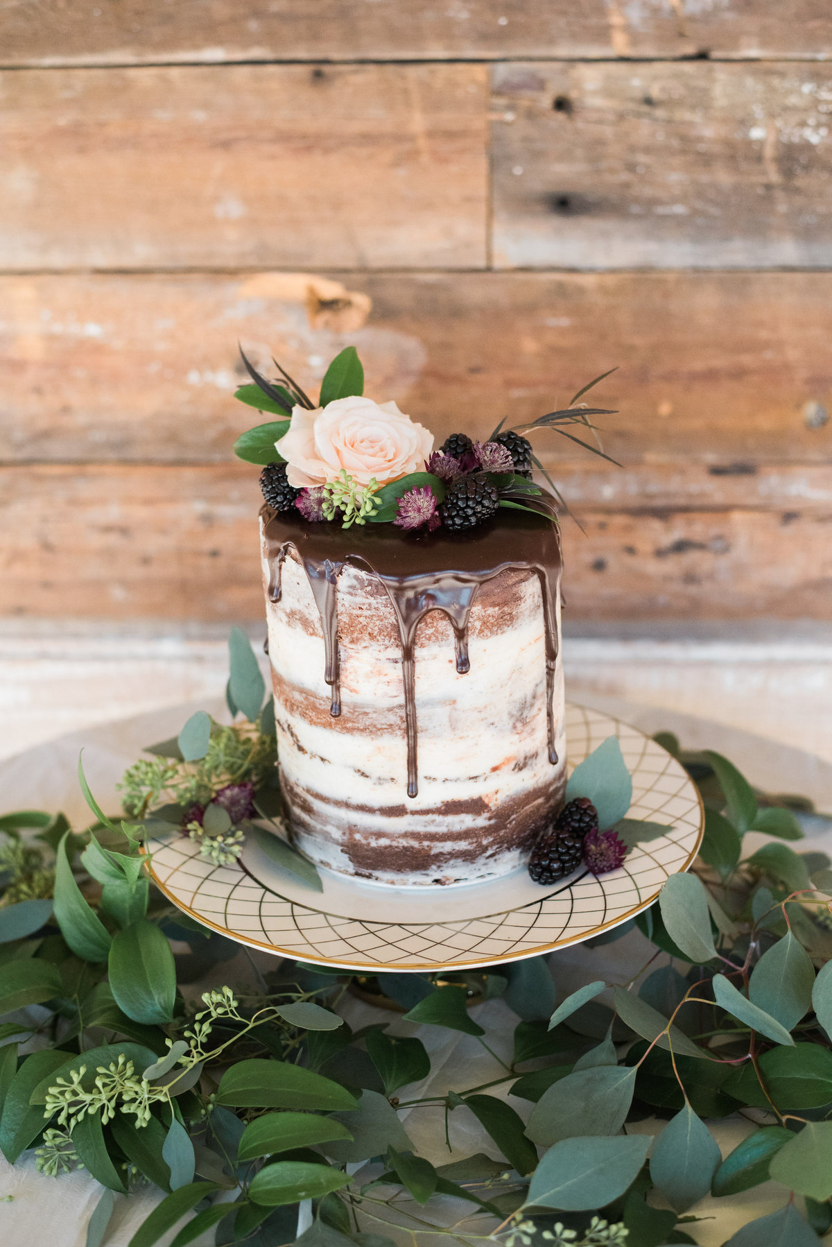 chocolate naked cake topped with florals and greenery
