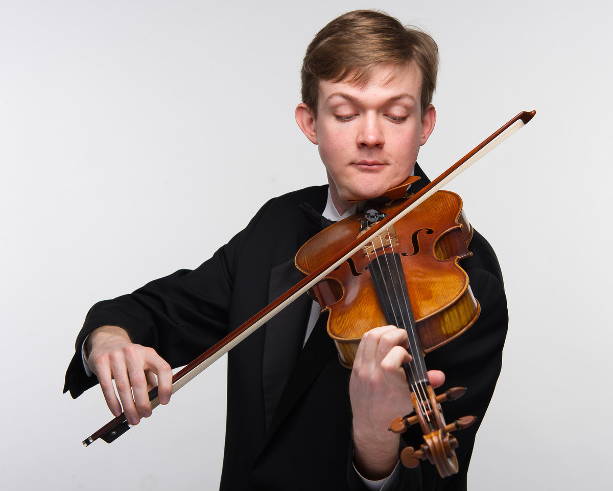 Studio portrait, Chicago violinist, male, playing against white background.