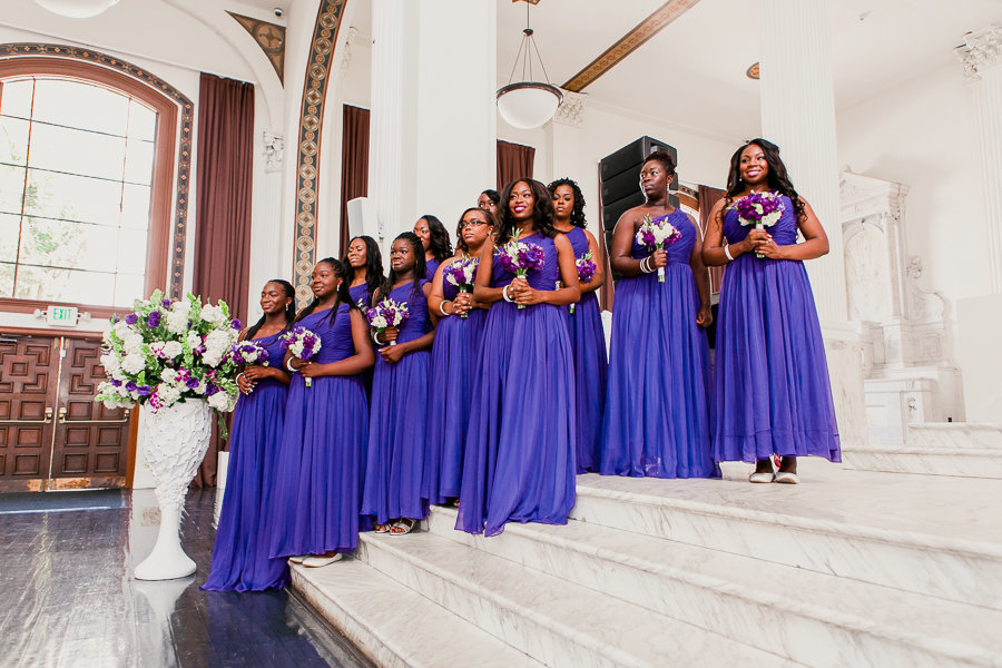 bridesmaids in purple dresses lined up inside church