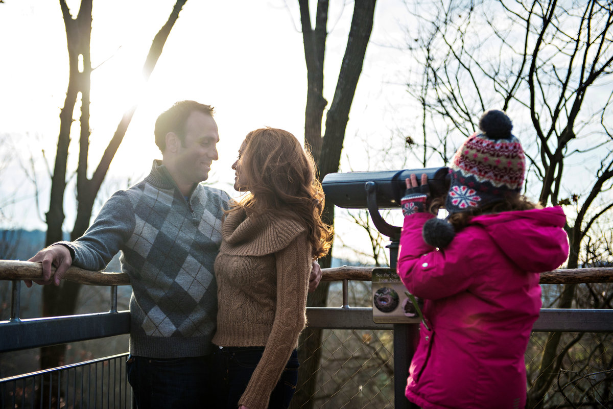 A little girl looks through a telescope at an engaged couple in morris arboretum.