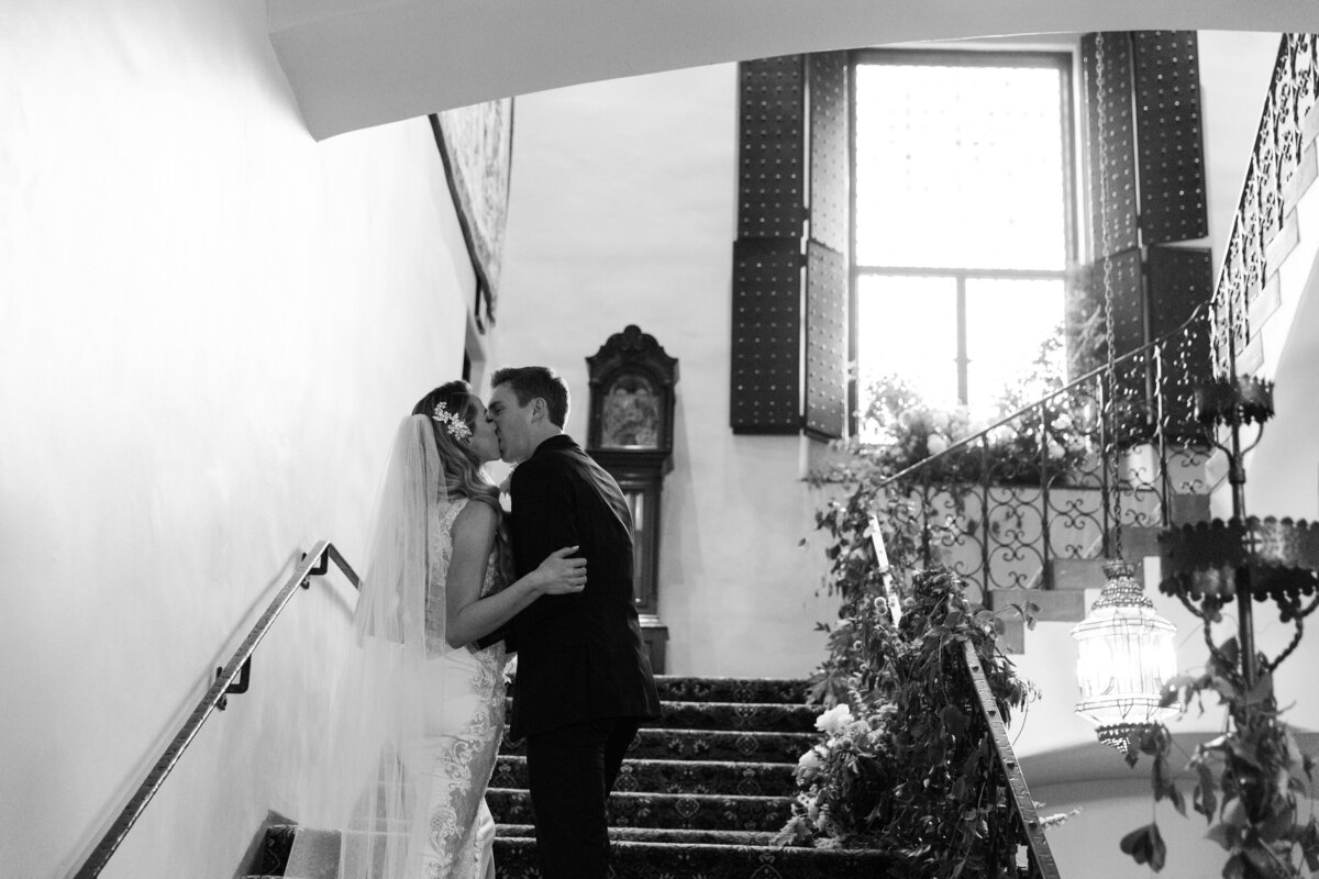 bride and groom kissing on staircase