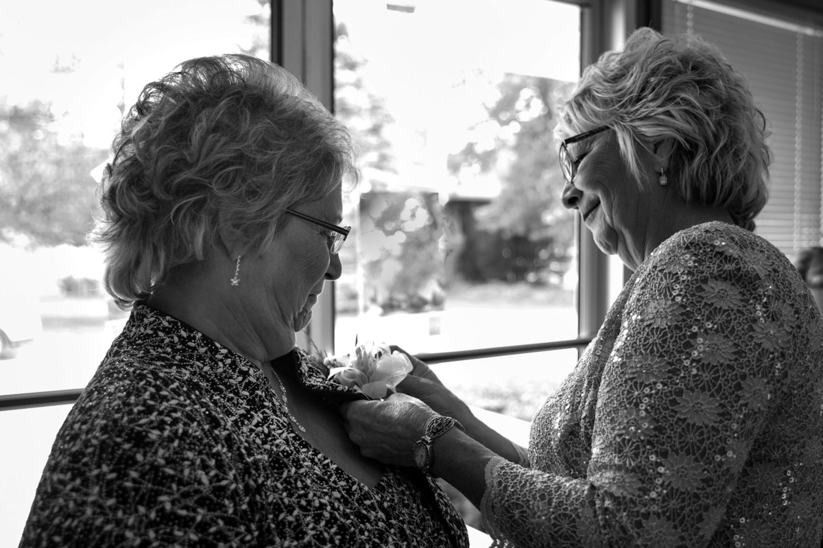 both mothers help each other with corsages