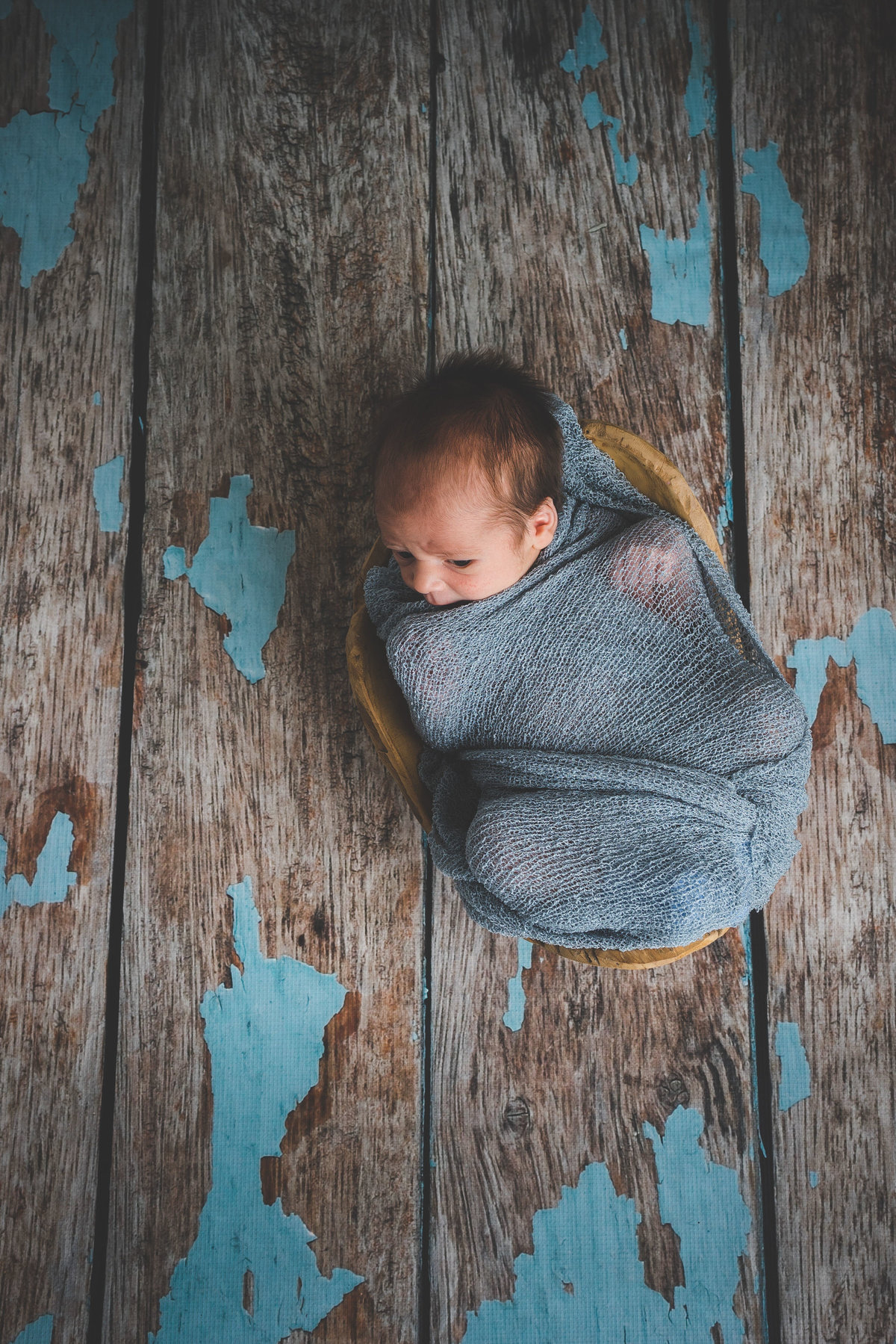 Newborn photography of baby wrapped in cheesecloth blanket in a bowl in a wooden floor.