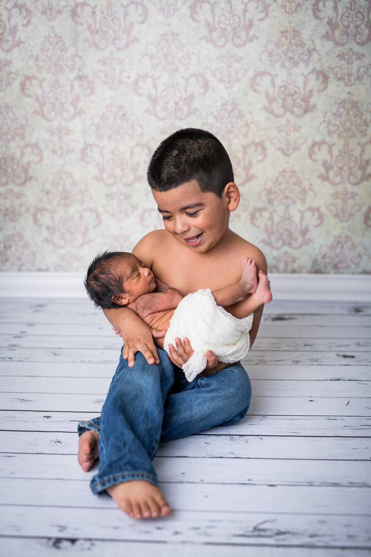 Brother holding newborn sister in his arms on s wooden floor in a photography studio