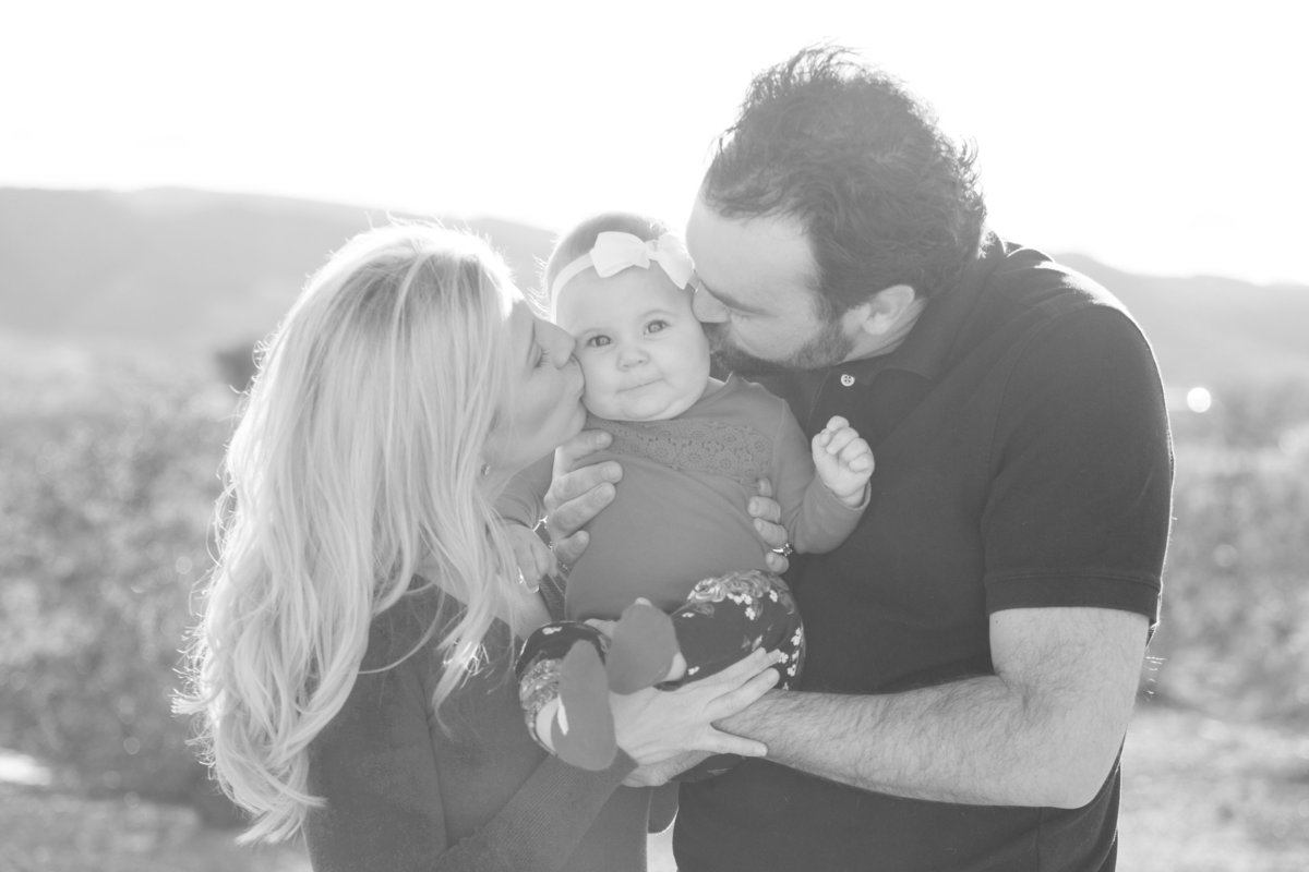 black and white photo of family giving baby kisses halley lutz photography