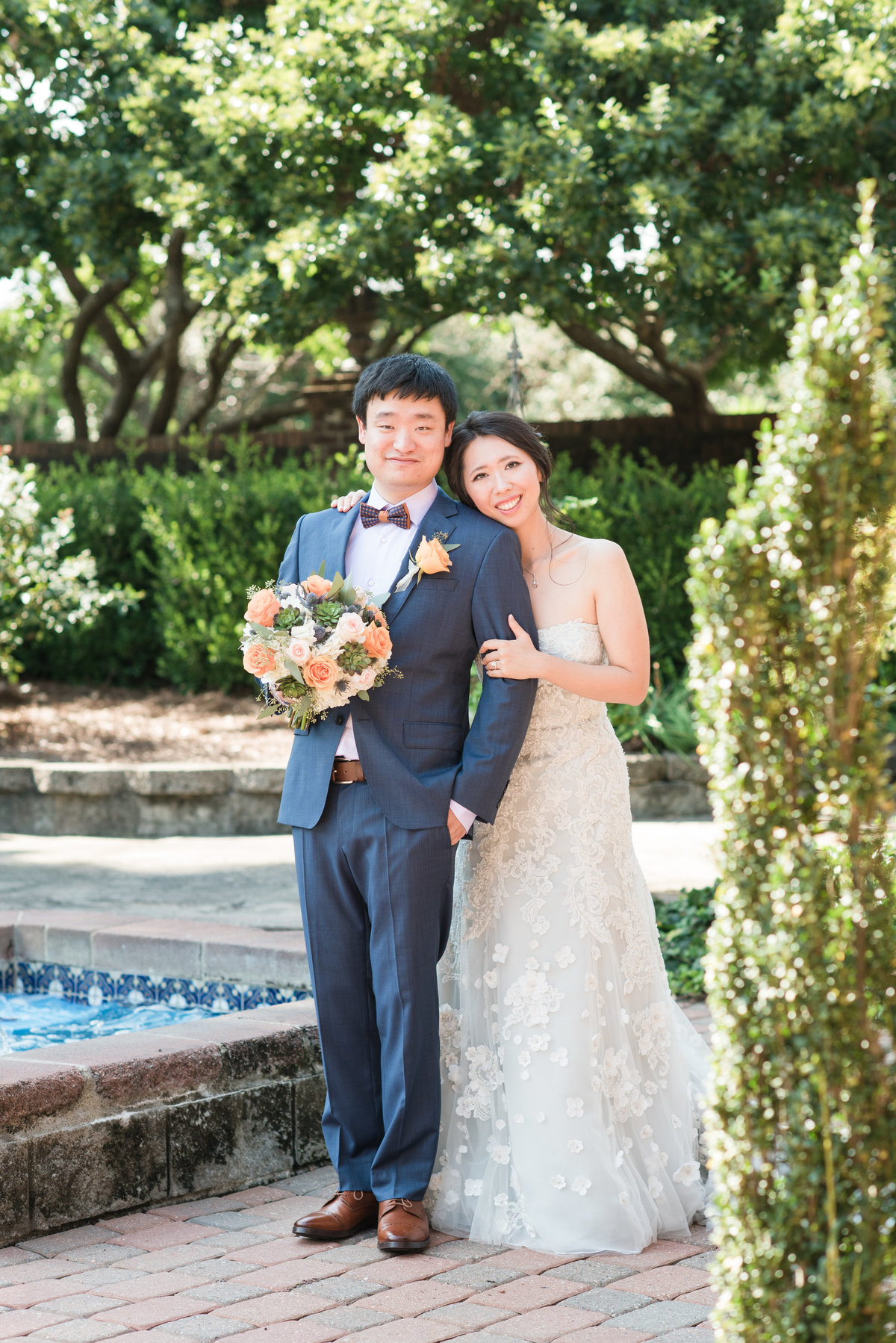 bride wearing light blue dress holding onto her husband wearing navy blue suit holding onto orange and green florals looking at the camera standing front of a fountain at Barclay Villa