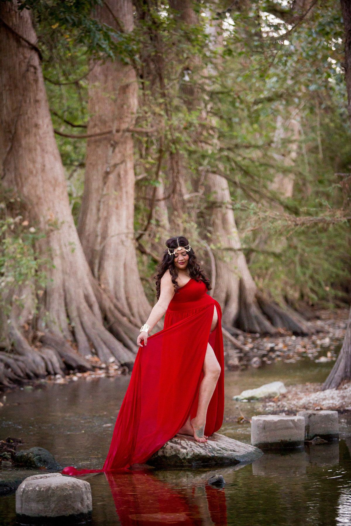 pregnant woman standing on a rock in a river wearing a red maternity dress in Cibolo Nature Center