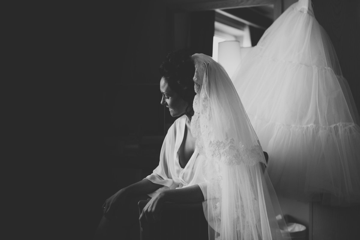 black and white photo of a bride in window light with veil in and dressing gown
