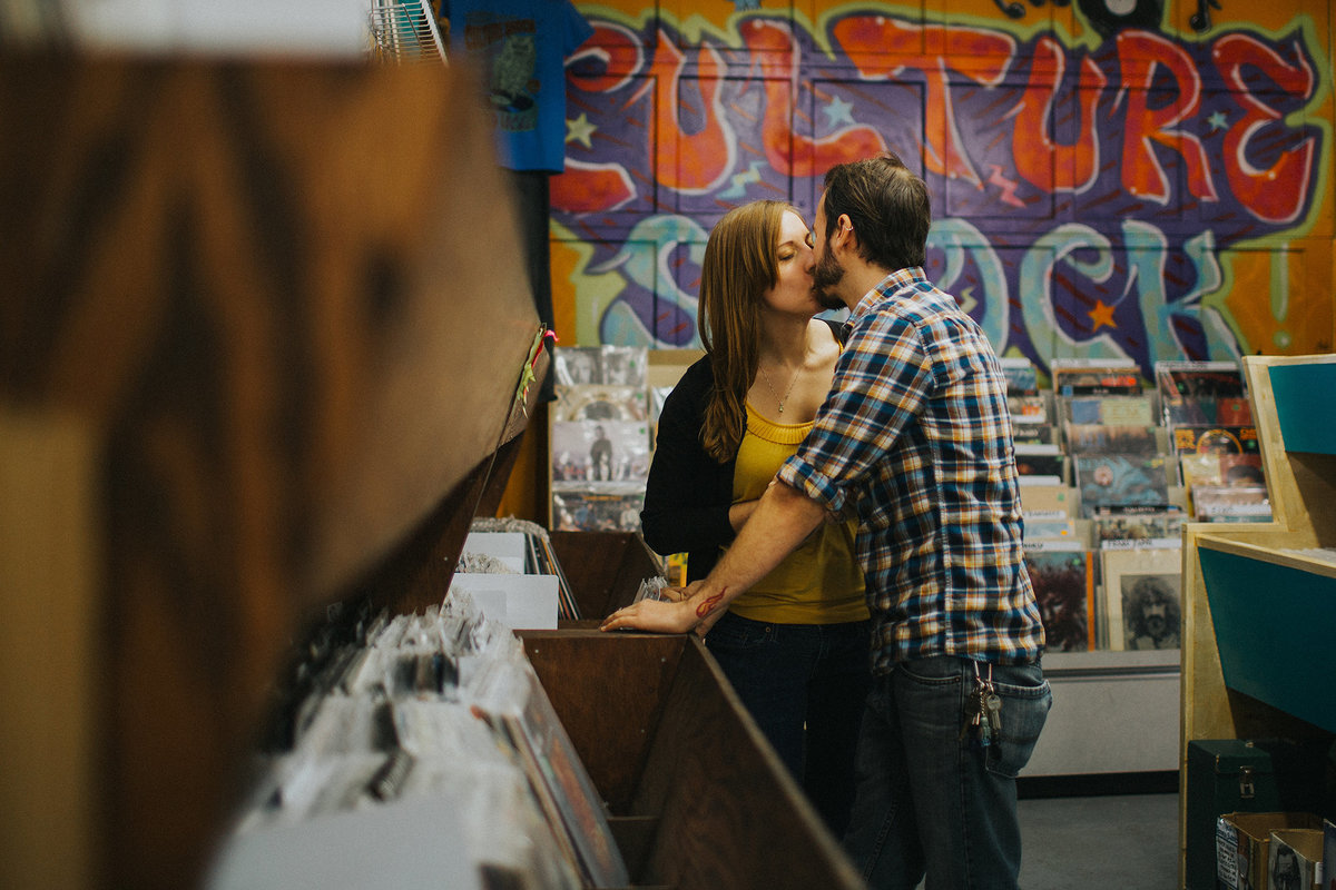 guy and girl kissing while browsing through records at culture shock records and gifts in rockford illinois