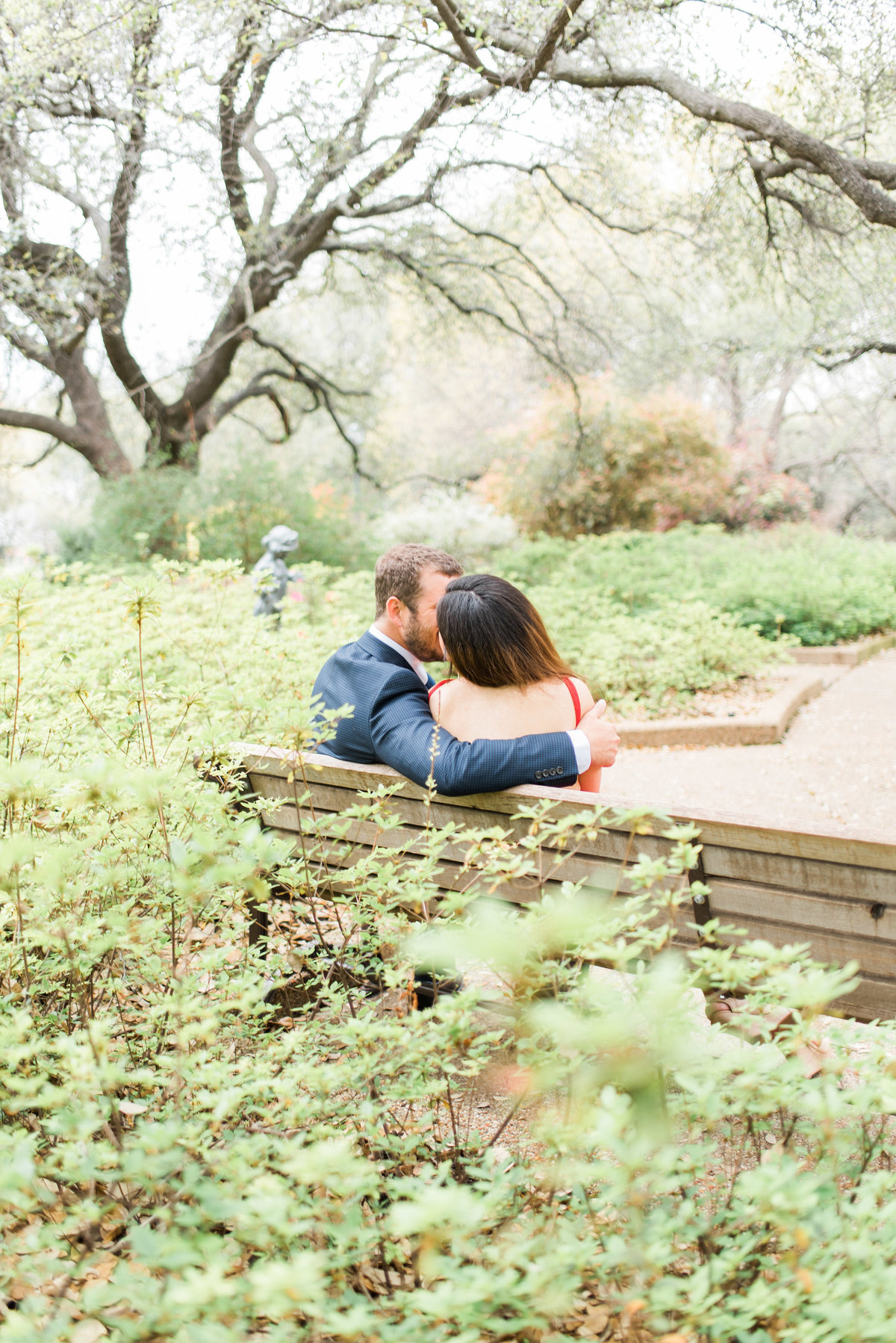 fort worth botanic garden engagement photo couple kissing on bench
