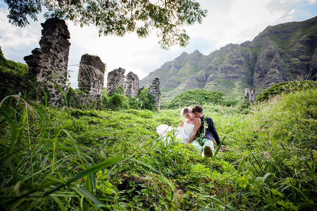 married couple in grassy field by ruins