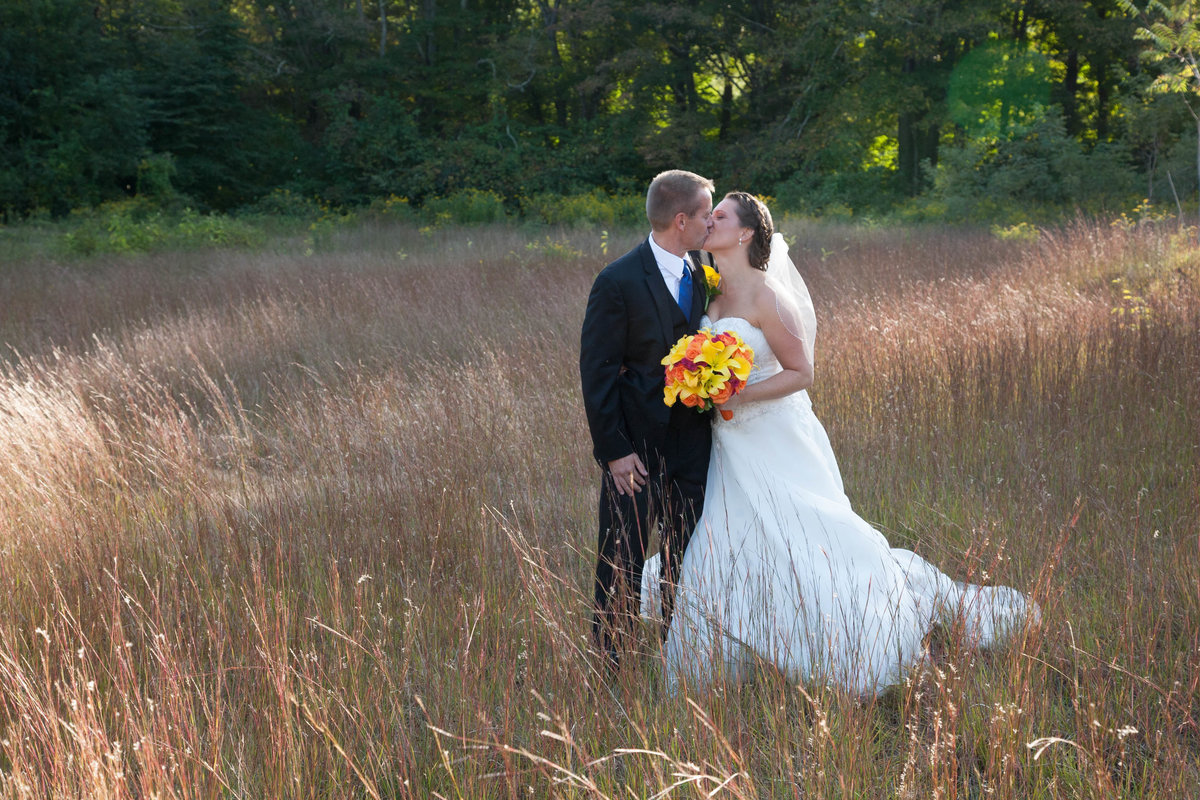 Bride and groom in field near The Riverhouse